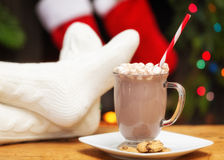 Relaxing With Hot Cocoa at Christmastime. Feet up on table relaxing in front of fire with hot cocoa and cookies at Christmastime royalty free stock photo