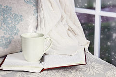 Relaxing Hot Drink. A hot relaxing cup of coffee or cocoa with an open book sitting on a comfortable chair with blanket. Extreme shallow depth of field royalty free stock photography