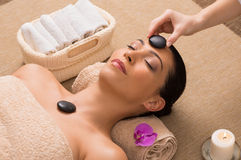 Relaxing Hot Stone Massage. Beautiful Woman Receiving A Hot Stone Massage On Her Face In A Spa stock photos