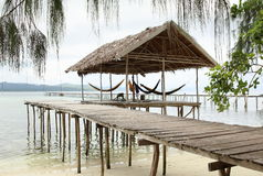 Relaxing Hut on the Sea Water. Relaxing hut in the style of papuan traditional house with palm leaves as the roof and some hammock hanging on the tropical sea Stock Image