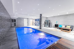 Relaxing indoor swimming pool with lighting and a corner for res. T. Luxury resort swimming pool with beautiful clean blue water and light effects around the Stock Photo
