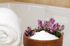 Relaxing Ingredients. Fresh pink purple heather flowers in a teak wood bowl with epsom salts on the edge of a bathtub with a rolled up white towel ready to take royalty free stock photo