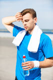 Relaxing after jog. Tired young woman drinking water and keeping eyes closed while standing outdoors Royalty Free Stock Photo