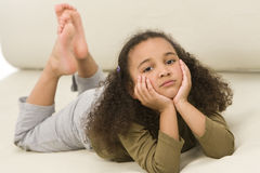 Relaxing Kid. A beautiful young mixed race girl laying down on a settee Stock Image