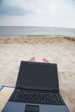 Relaxing with laptop on beach Stock Photo