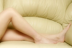 Relaxing Legs. View of womans legs as she relaxes on a leather settee Royalty Free Stock Photography