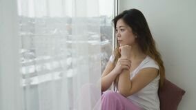 Relaxing leisure young pensive girl look window. Relaxing leisure. young pensive thoughtful teen girl sitting on the windowsill and looking out of the window stock footage