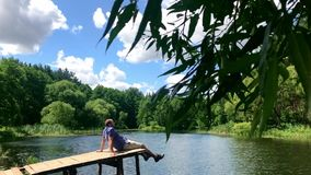 Relaxing for life, natural therapy concept. Young man people sitting relaxes to swing feets near water surface on side. Edge of wooden at nature river lake in stock footage
