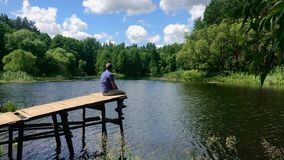 Relaxing for life, natural therapy concept. Young man people sitting relaxes to swing feets near water surface on side. Edge of wooden at nature river lake in stock video