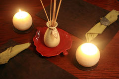 Relaxing lights. Two candles side by side a scented stick vase on a leaf with two place matt's, On a table Stock Image