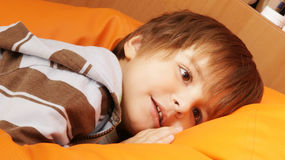Relaxing little boy. Happy little boy tacking rest after playing at home royalty free stock images