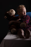 Relaxing little boy sitting with plush toy Stock Photos