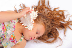 Relaxing little girl with seashell Stock Image