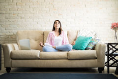 Relaxing in the living room with some meditation. Independent young woman sitting with her legs crossed doing some meditation in the living room Royalty Free Stock Photography