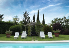 Relaxing location by the swimming pool under a blue sky Royalty Free Stock Image