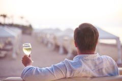 Relaxing man on the beach. Relaxing man with glass of white wine on the beach royalty free stock photos