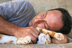 Relaxing man and cat. On sofa Royalty Free Stock Photography