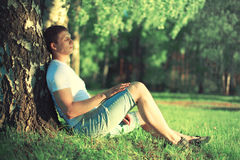 Relaxing man is dreaming under a tree with eyes closed meditating enjoying the warm evening sunset. In profile stock photography