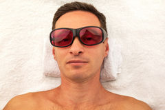 Relaxing man with glasses in spa salon laying on white towel. Relaxing handsome man with glasses in spa salon laying on white towel Stock Photography