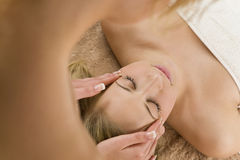 Relaxing Massage. A young woman relaxing at a health spa while having a massage Royalty Free Stock Image