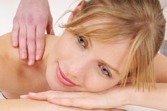 Relaxing massage. Beautiful blond woman receiving a relaxing massage and smiles royalty free stock photography