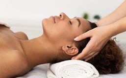 Relaxing Massage. Afro Woman Receiving Head Massage royalty free stock photo