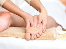 Relaxing massage on the foot  in spa salon. Indoors Stock Photography