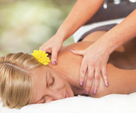 Relaxing massage for young beautiful woman Stock Photos
