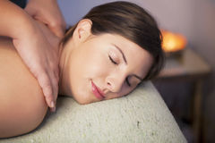 Relaxing massage. Young woman receiving relaxing back massage Royalty Free Stock Images