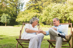 Relaxing mature couple sitting on sun loungers and talking Royalty Free Stock Image