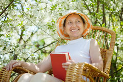 Relaxing  mature woman against bloom garden Stock Images