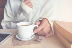 Relaxing moments , Cup of coffee and a book on wooden table in n Royalty Free Stock Photo