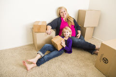 Relaxing Mother and Daughter In Empty Room With Moving Boxes Royalty Free Stock Photos