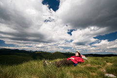 Relaxing on the mountain, under dramatic clouds Royalty Free Stock Photo
