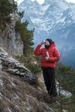 Relaxing mountaineer drinking hot drink from steel vacuum flask at snowy winter mountains background Royalty Free Stock Photo
