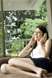 Relaxing With Music. An attractive young woman listens to music on headphones whilst sitting on the sofa at home Royalty Free Stock Image