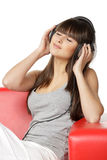 Relaxing with music. Young beautiful woman listening to music in headphones, enjoying and relaxing with closed eyes, over white background Royalty Free Stock Photography