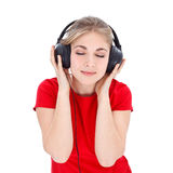 Relaxing with music. Nice girl in red t-shirt relaxing by listening music with headphones over white background Royalty Free Stock Image