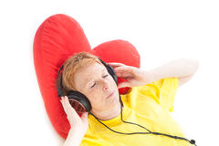 Relaxing with music. Portrait of an elder woman wearing headphones and lying with a red hearth pillow on a white background while listening music with closed Stock Photography