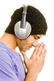 Relaxing music. Man listening to music with headphones while praying Royalty Free Stock Image