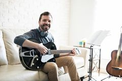 Relaxing music composer at home studio. Portrait of smiling young man sitting on sofa and playing music with guitar royalty free stock photos