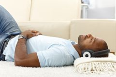 Relaxing with music on headphones. Portrait of casual guy relaxing with music on headphones at home, lying on floor Stock Photography