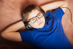 Relaxing with music at home. Cute kid lying on the carpet floor at home and listening to music with some headphones Stock Image