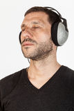 Relaxing Music. A man portrait listenin to music, with silver headphones Royalty Free Stock Image