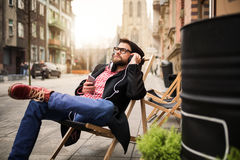 Relaxing with music. A photo of young man relaxing on the deckchair and listening music Royalty Free Stock Photo