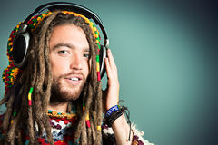 Relaxing music. Portrait of a happy rastafarian young man listening to music in headphones Royalty Free Stock Photography