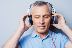Relaxing music time. Portrait of senior man in headphones listening to music keeping eyes closed while standing against grey background Stock Photos