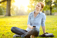 Relaxing Music - Woman in a Park. Casual young woman relaxes with music on a smartphone in a city park at sunset Stock Images