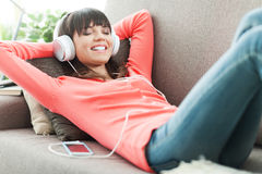 Relaxing music. Young attractive woman relaxing on the couch at home, she is listening to music with headphones Royalty Free Stock Image