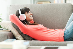 Relaxing music. Young attractive woman relaxing on the couch at home, she is listening to music with headphones Stock Photography